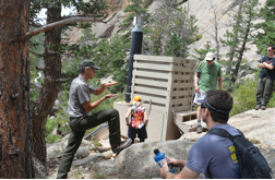 Conference participants visit a composting toilet in Rocky 