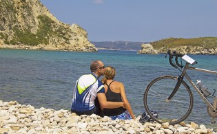 couple in Greece with water and bike