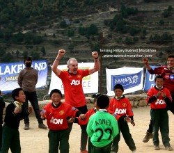 Kids in oversized Manchester United jerseys play football in a school ground in Namche with some participants and Everest Marathon team. It was a charity match where kids received player worn jerseys directly from Manchester United.