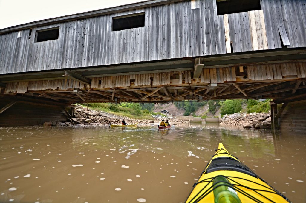 Kayaking with Red Rock Adventure beneath old covered bridges in St. Martins, New Brunswick in the Bay of Fundy