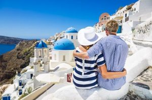 Happy young couple in village Oia on Santorini island, Greece.