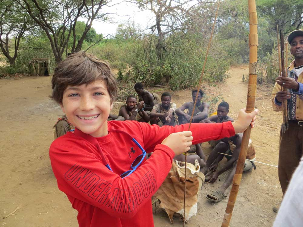 Young traveler experiences a modern day connection to our ancient indigenous roots with the Hadza bushmen of Tanzania. Courtesy Wildland Adventures.