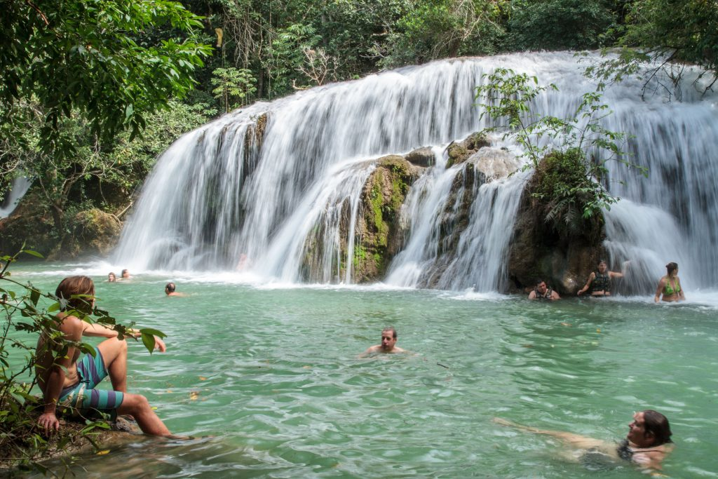 AdventureWeek Brazil participants enjoying a beautiful landscape and refreshing swim at one of the waterfalls in Estancia Mimosa. © ATTA / Hassen Salum